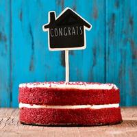 lavagna a forma di casa con il testo complimenti in una torta foto