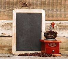 macinacaffè e lavagna vuota su sfondo di legno foto