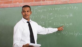 un uomo di colore che insegna matematica alla lavagna foto