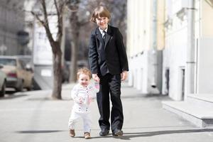 fratello e sorella che indossano abiti formali camminando sulla strada soleggiata foto