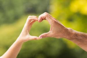 mani che formano il cuore foto