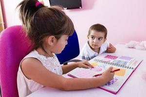 due bambini che studiano a casa foto