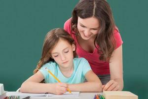 donna che assiste la figlia nello studio foto