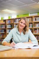 bella studentessa che studia in biblioteca foto