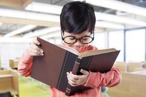 piccolo studente intelligente che studia con il libro in classe foto