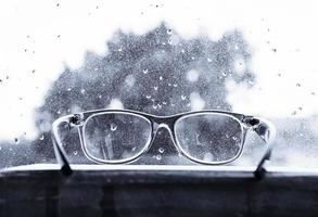 occhiali da lettura sopra la finestra piovosa in bianco e nero foto