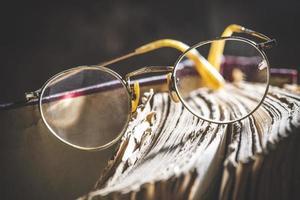vecchi occhiali rotondi vintage e libro foto