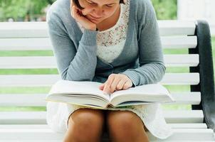 giovane donna legge su una panchina nel parco foto