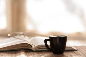 i bicchieri della tazza di caffè riposano sul libro aperto foto