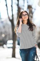 bellissima modella cammina con il telefono foto