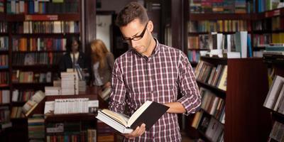 giovane uomo bello che legge un libro foto