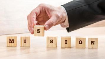 primo piano dell'uomo d'affari che crea una missione di parola con sette di legno foto