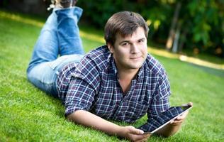 uomo disteso sull'erba al parco e utilizzando la tavoletta digitale foto
