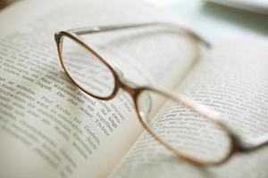 libro aperto e occhiali da vista foto