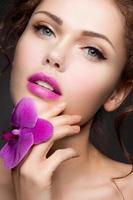 Ritratto del primo piano di bella donna con trucco luminoso