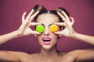 modella, una donna con trucco luminoso e biscotti colorati scherzando.