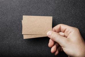 mano dell'uomo che tiene due biglietti da visita artigianali sul foto