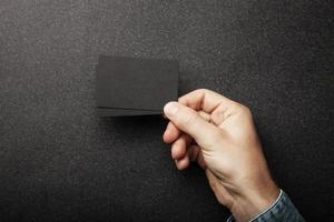 mano dell'uomo che tiene due biglietti da visita sul nero foto