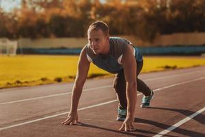 uomo in piedi in postura pronto a correre sul tapis roulant. foto