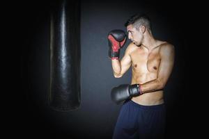 uomo muscoloso allenamento con sacco da boxe in palestra