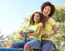 madre e figlia cavalcando un'altalena nel parco foto