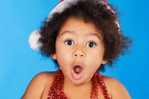 piccolo bambino sorpreso in cappello di natale foto