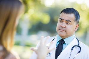 medico o infermiere maschio ispanico che parla con un paziente