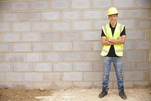 Ritratto del muratore maschio sul cantiere foto