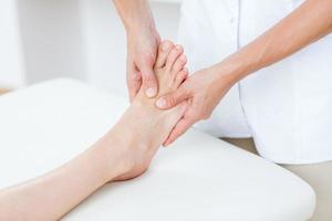 Fisioterapista che fa massaggio ai piedi foto
