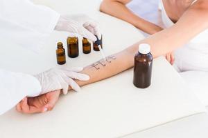 medico che fa il test della puntura della pelle al suo paziente foto
