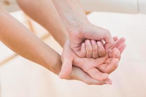 Fisioterapista che fa massaggio alle mani