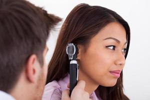 medico che esamina l'orecchio del paziente con otoscopio
