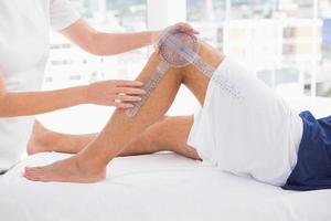medico esaminando la gamba uomo foto