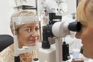 la giovane donna sta facendo una visita medica all'optometrista foto