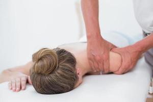 Fisioterapista che fa massaggio del braccio al suo paziente foto