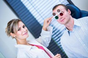 giovane uomo che ha gli occhi esaminati da optometrici foto