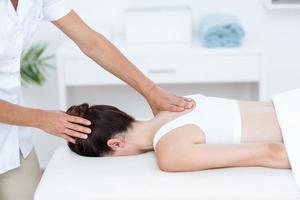 Fisioterapista che fa massaggio alla spalla foto