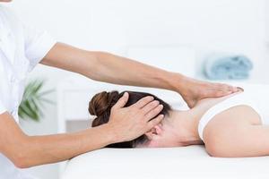Fisioterapista che fa massaggio al collo foto