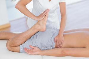 Fisioterapista che fa massaggio alle gambe al suo paziente foto