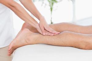 Fisioterapista che fa massaggio al polpaccio per il suo paziente foto