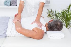 Fisioterapista che fa massaggio alla spalla al suo paziente foto