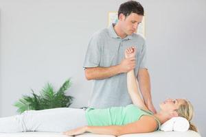 fisioterapista bello che tratta la spalla dei pazienti foto