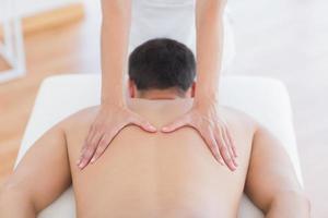 Fisioterapista che fa massaggio alla schiena al suo paziente foto