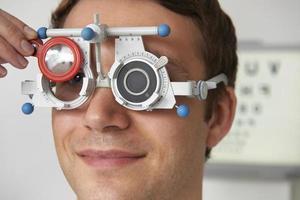 uomo con test di vista a optometrista foto