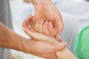 vicino del fisioterapista che impasta la mano dei pazienti foto