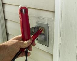 elettricista collauda una presa esterna foto