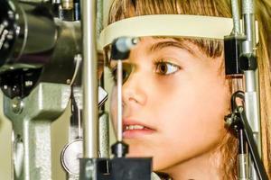 piccola ragazza che fa la prova dell'esame degli occhi foto