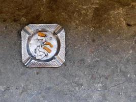 Posacenere di metallo con mozziconi di sigaretta in primo piano foto
