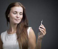 bella donna sorridente con ecigarette foto