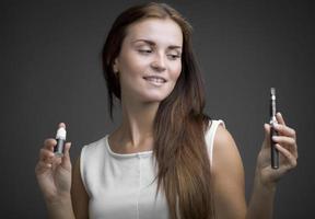 donna che tiene e-sigaretta e bottiglia di liquido foto